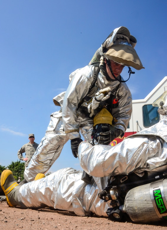 U.S. Air Force Airman 1st Class Gregory Pease, 612th Air Base Squadron firefighter, provides simulated medical attention to U.S. Air Force Senior Airman Collin Lorash, 612th Air Base Squadron firefighter, during a hazardous material exercise on Soto Cano Air Base, Honduras, Feb. 10, 2015. The training exercise was held to guarantee members assigned to the 612th ABS Fire Department are compliant with the Department of Defense's requirement that all Air Force firefighters are certified to the hazmat technical level. (U.S. Air Force photo/Tech. Sgt. Heather Redman)