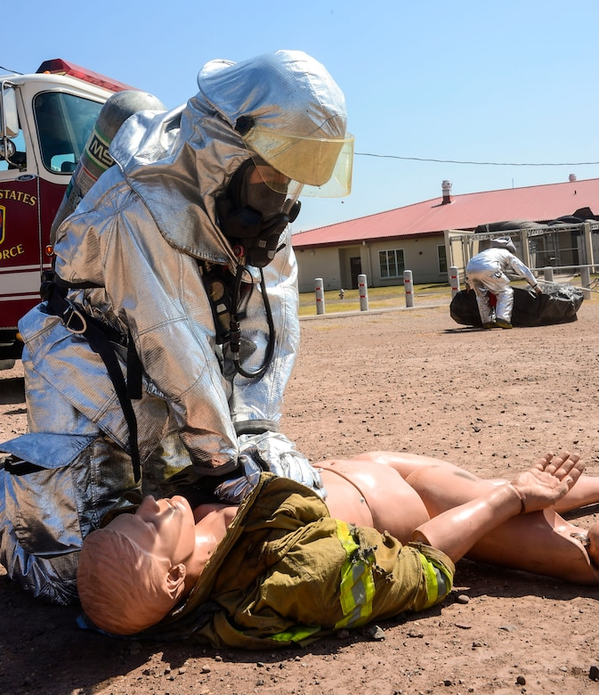U.S. Air Force Senior Airman Collin Lorash, 612th Air Base Squadron firefighter, provides medical attention to a dummy during a hazardous material exercise on Soto Cano Air Base, Honduras, Feb. 10, 2015. The training exercise was held to guarantee members assigned to the 612th ABS Fire Department are compliant with the Department of Defense's requirement that all Air Force firefighters are certified to the hazmat technical level. (U.S. Air Force photo/Tech. Sgt. Heather Redman)