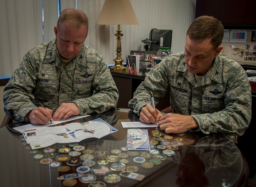 Col. Jeffrey DeVore, Joint Base Charleston commander, and Col. John Lamontagne, 437th Airlift Wing commander, sign their Air Force Assistance Fund contribution forms Feb. 10, 2015, at JB Charleston – Air Base, S.C. The AFAF is an annual effort to raise funds toward charitable affiliates that support Air Force families in the event of emergencies.   (U.S. Air Force photo / Senior Airman Tom Brading)
