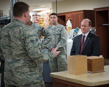 Senior Airman Nicholas Wavra, a services Airman assigned to the Air Force Mortuary Affairs Operations Dress and Restoration section, explains how he helps prepare uniforms for fallen warriors to Sen. Chris Coons of Delaware Feb. 9, 2015, during the senator's visit to Dover Air Force Base, Del. Wavra and other AFMAO Airmen briefed Coons on the unique tasks performed at the Department of Defense's sole port mortuary. (U.S. Air Force photo by Capt. Ray Geoffroy)