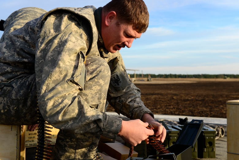 A U.S. Army National Guard soldier assigned to the 1st Battalion, 169th Aviation Regiment, Ft. Bragg, N.C., prepares the bullets for a M240 machine gun at Poinsett Electronic Combat Range, Sumter, S.C., Feb. 6, 2015. Military members can also utilize the electronic warfare capabilities offered at the range which shoots simulated munitions at the aircraft giving the pilots a safe environment to practice different scenarios. (U.S. Air Force photo by Airman 1st Class Diana M. Cossaboom/Released)