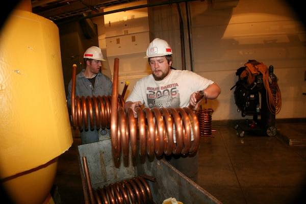 Electrician Connor Florey (left) asssists Mechanic Bryce Stasch (right) with new cooling coils to be installed on the hydropower units at Ft. Randall Dam.