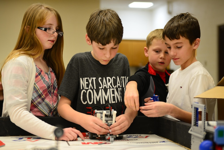 "Students from Cannon's For Inspiration and Recognition of Science and Technology ""FIRST""  Lego League teams work together to modify their robot Jan. 29, 2015, at Cannon Air Force Base, N.M. Building and programming robots for competition teaches team members skills like critical thinking, team building, and the application of real-word math and science concepts. (U.S. Air Force photo/Airman 1st Class Shelby Kay-Fantozzi)"