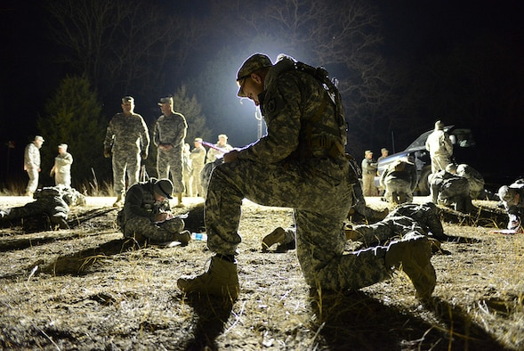A soldier from the Army National Guard plots the points on his map using available light during the twilight land-navigation course at the 2015 Best Warrior Competition at Camp Swift, Texas, Feb. 7, 2015. The course started at 5a.m. and finished at daybreak. The competition determines the best of the best warrior amongst Army and Air National Guardsmen. (photo by Master Sgt. Charles Hatton/released)