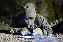 U.S. Air Force Senior Airman Michael Renteria, 147th Air Support Operations Squadron, Texas Air National Guard, plots the points on his map during the twilight land-navigation course at the 2015 Best Warrior Competition at Camp Swift, Texas, Feb. 7, 2015. The competition determines the best of the best warrior amongst Army and Air National Guardsmen. (photo by Master Sgt. Charles Hatton/released)