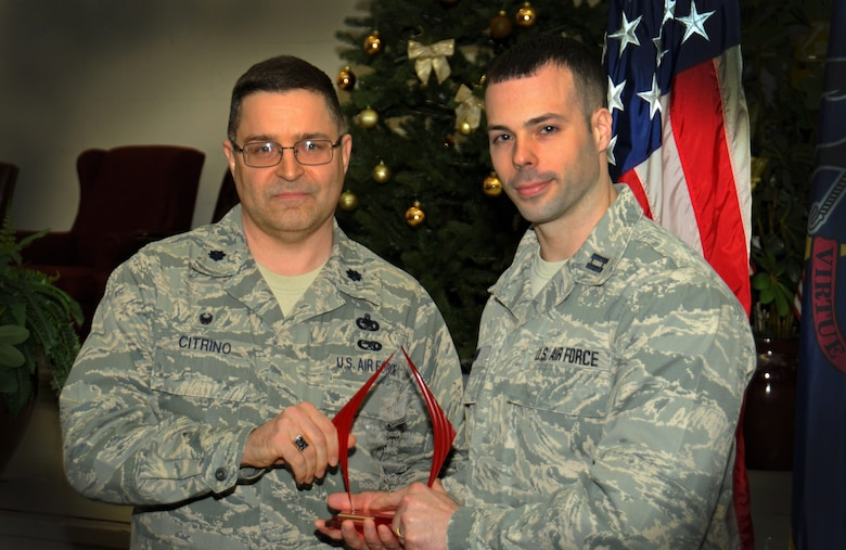 Lt. Col. RIchard Citrino, 111th Logistics Readiness Squadron commander, hands an award to Capt. Steven Good, 111th LRS deployment and distribution flight commander, as the 111th Attack Wing recognized five 2014 Annual Award recipients during a ceremony held here Feb. 8, 2015 at the headquarters building, Horsham Air Guard Station , Pa. The categories in which the Guardsmen competed were Airman, Noncommissioned Officer, First Sergeant, Senior NCO and Company Grade Officer of the Year. The winners each received and plaque and certificate to recognize their achievements.(U.S. Air National Guard photo by Staff Sgt. Michael Stauffer/Released)
