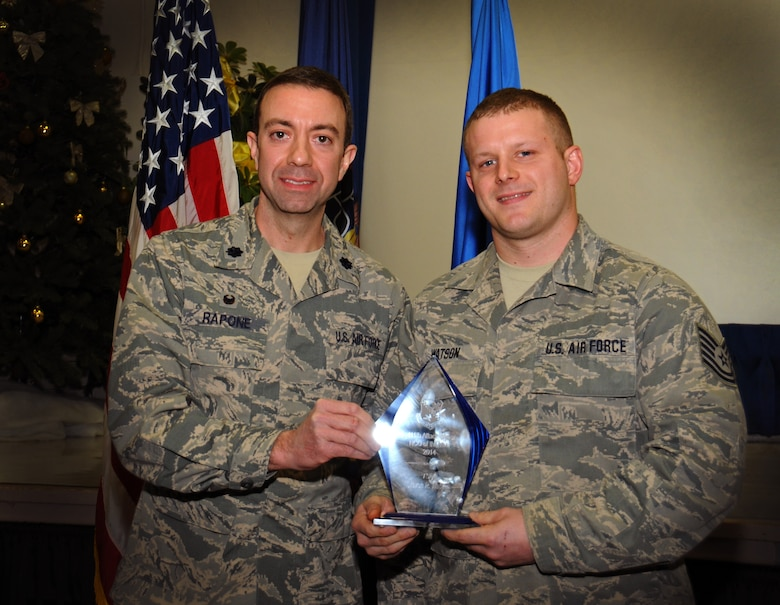 Lt. Col. Geno Rapone, 270th Engineering and Installation Squadron commander, hands an award to Tech. Sgt. Steven Watson, 207th EIS cable and antenna systems specialist, as the 111th Attack Wing recognized five 2014 Annual Award recipients during a ceremony held here Feb. 8, 2015 at the headquarters building, Horsham Air Guard Station , Pa. The categories in which the Guardsmen competed were Airman, Noncommissioned Officer, First Sergeant, Senior NCO and Company Grade Officer of the Year. The winners each received and plaque and certificate to recognize their achievements.(U.S. Air National Guard photo by Staff Sgt. Michael Stauffer/Released)