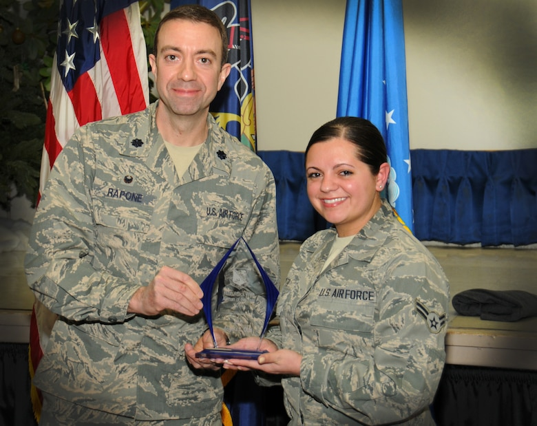 Lt. Col. Geno Rapone, 270th Engineering and Installation Squadron commander, hands an award to Airman 1st Class Angela Otto, 270th EIS administrative assistant, as the 111th Attack Wing recognized five 2014 Annual Award recipients during a ceremony held here Feb. 8, 2015 at the headquarters building, Horsham Air Guard Station , Pa. The categories in which the Guardsmen competed were Airmen, Noncommissioned Officer, First Sergeant, Senior NCO and Company Grade Officer of the Year. The winners each received and plaque and certificate to recognize their achievements.(U.S. Air National Guard photo by Staff Sgt. Michael Stauffer/Released)