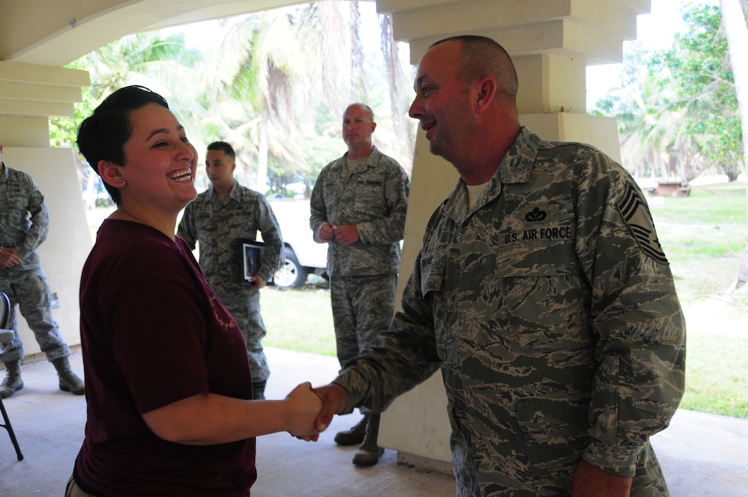 U.S. Air National Guard Airman 1st Class Jessica Ochoa from the 146th Airlift Wing Civil Engineering Squadron receives a coin from Chief Master Sgt. Kirk Rhame at Tarague Beach, Andersen AFB Guam on Februrary 11, 2015. (U.S. Air National Guard photo by Airman 1st Class Madeleine Richards/Released)