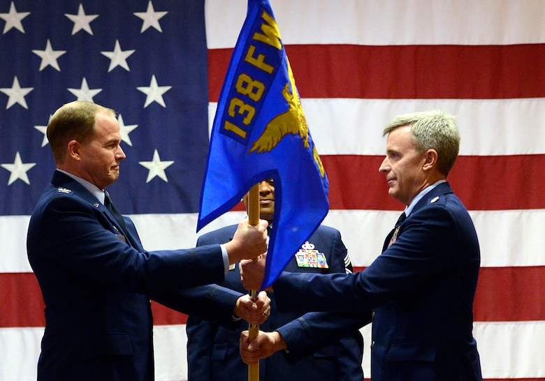 Col. Rick Poplin accepts the 138th Operations Group (OG) guidon from Col. David B. Burgy, 138th Fighter Wing commander, during a change of command ceremony for the 138th OG, Feb. 8, 2015, Tulsa Air National Guard base, Tulsa, Okla.  The ceremony was officiated by Burgy and was held in the aerospace dining facility during the wing's February unit training assembly.  (U.S. National Guard photo by Master Sgt.  Mark A. Moore/Released)