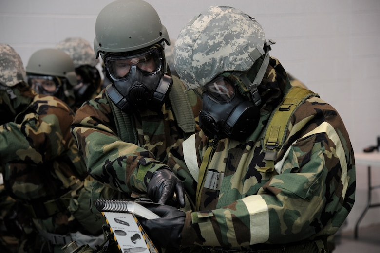 Two 127th Wing Airmen review information inside the Airman's Manual while dressed in Mission Oriented Protective Posture, or MOPP gear, during an expeditionary skills training day at Selfridge Air National Guard Base, Mich., Feb 8, 2015. Every three years, all airmen must attend expeditionary skills refresher training, in order to maintain their readiness.  (U.S. Air National Guard photo by Senior Amn. Ryan Zeski)