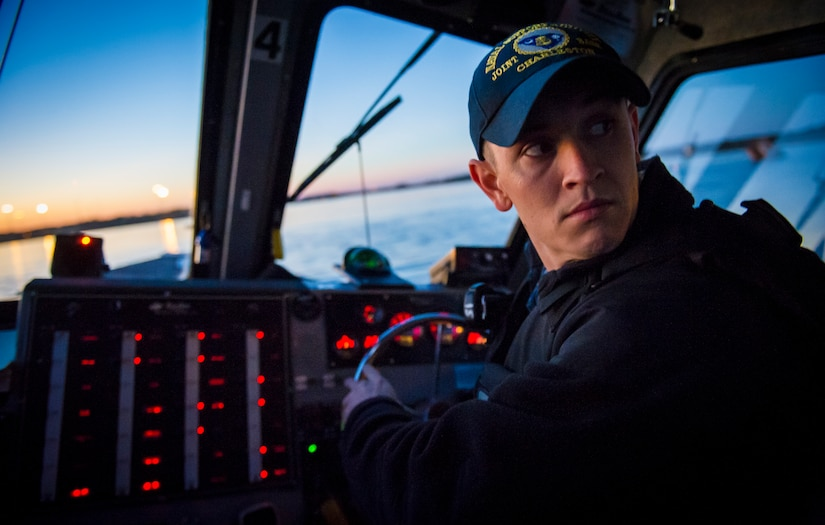 Master at Arms 2nd Class Michael Harkey, 628th Security Force Squadron level two coxswain, listens for orders Feb. 11, 2015, at Dock Charlie on Joint Base Charleston – Weapons Station, S.C. The night operation demonstrated the Defenders' insertion and extraction capabilities, while increasing teamwork and camaraderie.  (U.S. Air Force photo/Airman 1st Class Clayton Cupit)