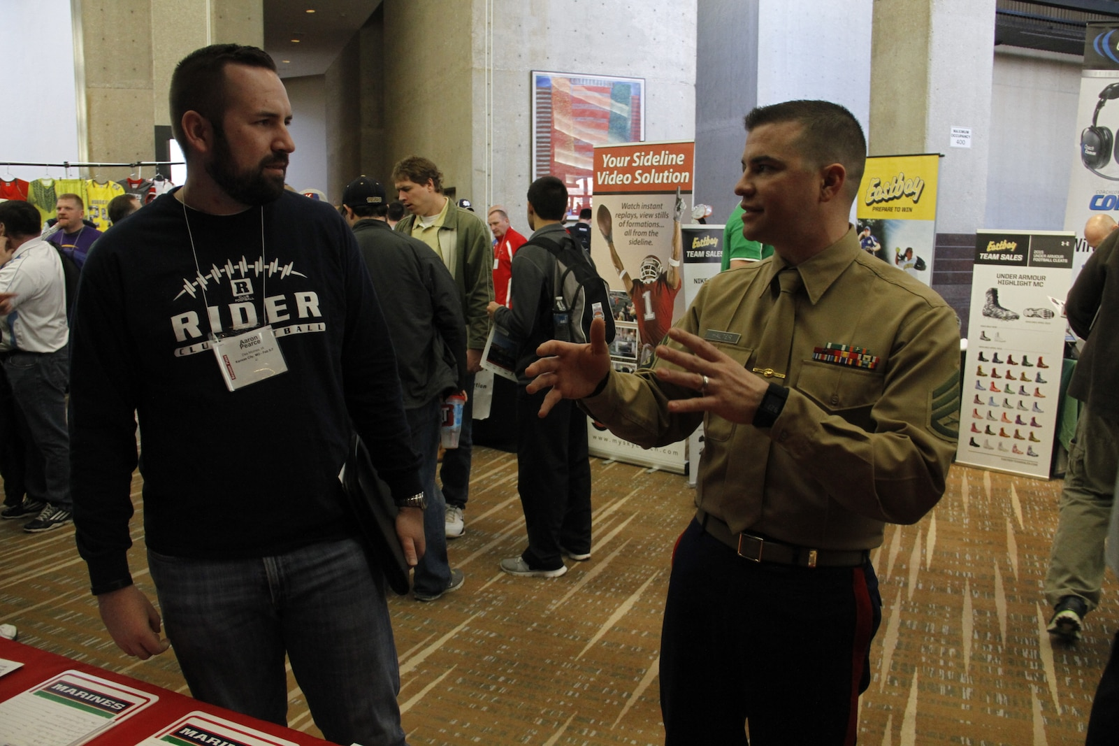 Staff Sgt. Adam Halter, Marine Corps Recruiting Station Kansas City, Recruiting Sub-Station St. Joseph staff noncommissioned officer-in-charge, speaks with a coach about the Combat Fitness Test during the Glazier Clinic at the Westin Crown Center Feb. 6, 2015. The CFT is used to test both the physical endurance as well as mental endurance of Marines. It is in this way that coaches may request recruiters to come to their schools and perform the CFT with their players to determine how effective their own conditioning programs have worked and also to build teamwork through several events outside of the normal routine of football practice.