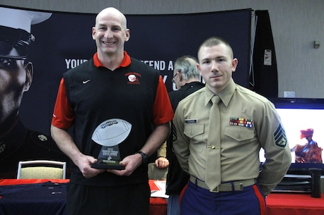 Jason Swift, Shawnee Heights High School Thunderbirds head football coach, stands with Staff Sgt. Skyler Tooker, a Marine Corps Recruiting Station Kansas City, Recruiting Sub-Station Topeka canvassing recruiter, after being presented the Semper Fi Coach Award during the Glazier Clinic at the Westin Crown Center Feb. 6, 2015. Swift was presented the award not just for his on-the-field accomplishments but the way he has influenced players in his community and molded their character on and off the field. Swift has led the Thunderbirds to eight district championships and 10 straight playoff appearances in his 12 years as head coach.