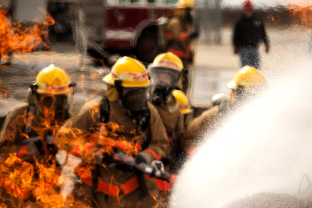 Airman 1st Class Onnie McSpadden leads his group to extinguish a fire Feb. 3, 2015, at Goodfellow Air Force Base, Texas.  McSpadden is a 127th Michigan Air National Guard firefighting apprentice. (U.S. Air Force photo/ Senior Airman Scott Jackson)
