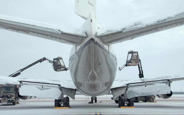 Senior Airmen Riley Neads and Kyle Kindig operate air cannons from deicing trucks to blow snow off of an OC-135 Open Skies aircraft Feb. 3, 2015, at Offutt Air Force Base, Neb. Additional maintenance time is typically needed during winter operations to heat the aircraft and to remove snow and ice. Neads and Kindig are assigned to the 83rd Aircraft Maintenance Unit, 55th Aircraft Maintenance Squadron. (U.S. Air Force photo/Delanie Stafford)