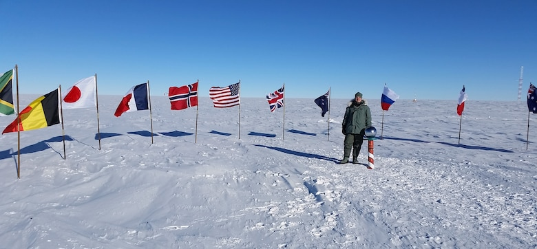 Senior Airman Lucas McEntire, an aircraft fuels systems mechanic with the 103rd Maintenance Squadron, stands next to the South Pole in Antarctica Nov. 14, 2014. The ceremonial pole is actually 100 feet from the geographical South Pole, said McEntire, and the temperature that day was minus 40 degrees, the exact temperature at which Centigrade and Fahrenheit are the same. (U.S. Air National Guard photo courtesy of Senior Airman Lucas McEntire)