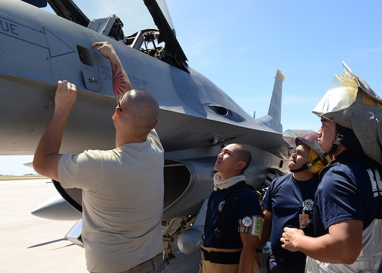 An F-16 maintainer deployed from the 35th Fighter Wing, Misawa Air Base, Japan, shows Saipan firefighters various hazardous points on a F-16 Fighting Falcon during training Feb. 12, 2015, at the Saipan International Airport, Saipan in the Commonwealth of Northern Marianas Islands approximately 130 miles north of Guam. The training was geared towards preparing Saipan first responders for a runway emergency involving the F-16. (U.S. Air Force photo by Senior Airman Cierra Presentado/Released)