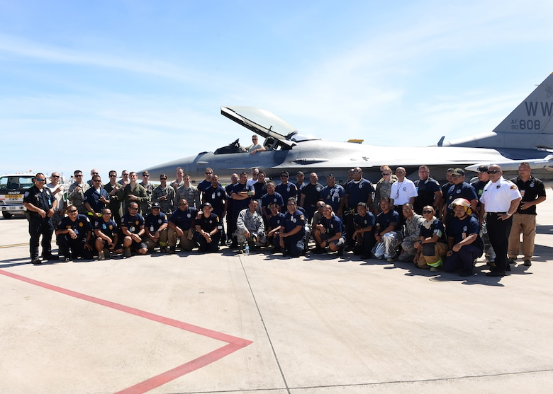Members of Andersen Air Force Base, Guam, Saipan International Airport firefighters and F-16 pilots and maintainers deployed from the 35th Wing, Misawa Air Base, Japan, gather for a picture after training Feb. 12, 2015, at Saipan International Airport, Saipan in the Commonwealth of Northern Marianas Islands. The training was geared towards preparing Saipan first responders for a runway emergency involving the F-16. (U.S. Air Force photo/Senior Airman Cierra Presentado)