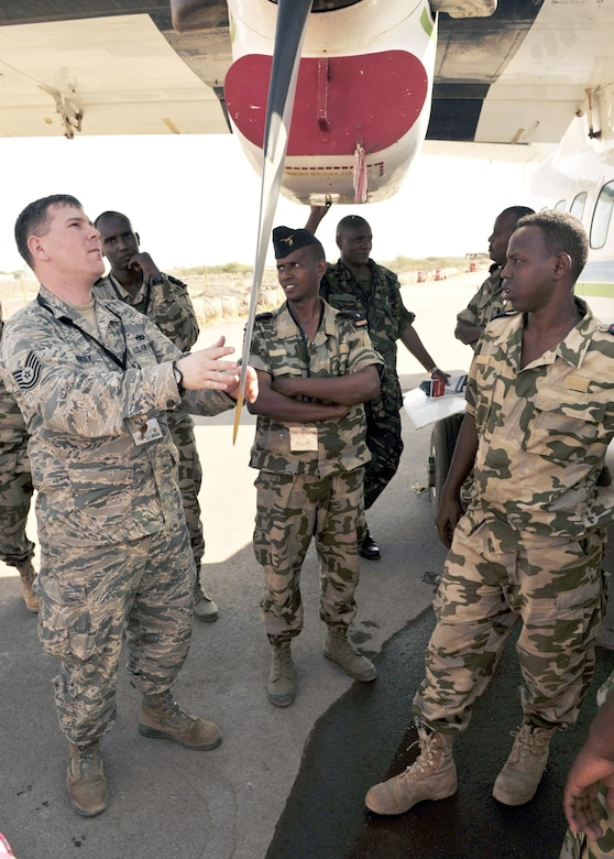 Tech. Sgt. Albert Kirkey, left, talks with Djiboutian air force members about maintenance procedures for the Let L-410 Turbolet aircraft during African Partnership Flight-Djibouti (APF) Feb. 9, 2015, at Djibouti Air Base. APF is the premiere program to bring together partner nations to increase cooperation and interoperability, which fosters stability and security throughout the continent. Kirkey is an aircraft maintenance adviser with the 818th Mobility Support Advisory Squadron. (U.S. Air Force Photo/Tech. Sgt. Ian Dean)