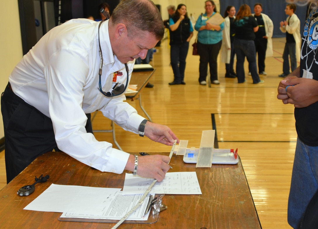 "ALBUQUERQUE, N.M., -- Reginald Bourgeois, the District's STEM coordinator and a judge at the 2015 Central New Mexico Regional Science Olympiad, measures a student's plane Jan. 31. The planes had to meet specific minimum weight and size limits to be eligible to compete in ""The Wright Stuff"" event."