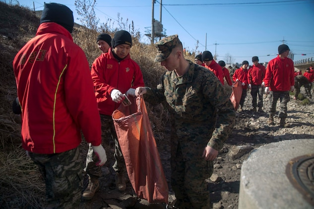 U.S. Marine Lance Cpl. Michael R. Guthrie, right, picks up trash alongside Republic of Korea Marines during Korean Marine Exchange Program 15-17 Feb. 12 in Pohang, ROK. U.S. Marines have a strong belief that, upon leaving somewhere, they must leave it in better condition than when they arrived. Marines with 3rd Battalion, 3rd Marine Regiment decided to put this belief into action. From planning to execution, KMEP 15-17 has been a bilateral and collaborative effort between ROK and U.S. Marine Corps forces. Guthrie, from St. Louis, Missouri, is an intelligence specialist with 3rd Battalion, 3rd Marine Regiment, currently assigned to 4th Marine Regiment, 3rd Marine Division, III Marine Expeditionary Force under the unit deployment program. The ROK Marines are with the 1st Engineer Battalion, 1st ROK Marine Division.