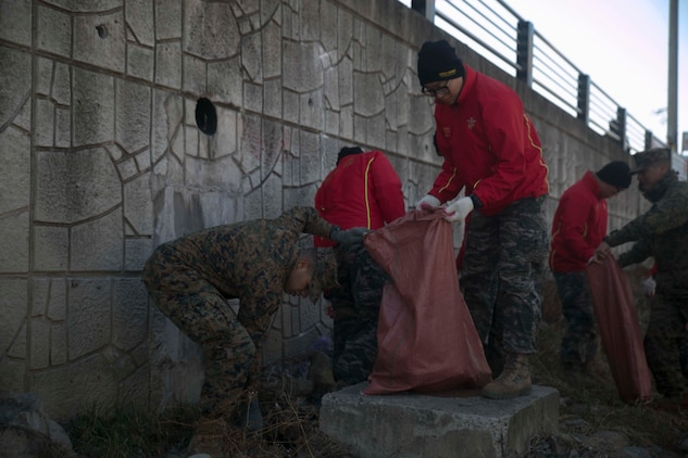 U.S. Marine Cpl. Lomatthias M. McNealy, left, picks up trash alongside Republic of Korea Marines during Korean Marine Exchange Program 15-17 Feb. 12 in Pohang, ROK. The Marines were tasked with cleaning sidewalks, alleyways, dried-up riverbeds and other places where trash accumulates in the city. KMEP 15-17 is a regularly-scheduled, bilateral, small-unit training exercise, which enhances the combat readiness and interoperability of ROK and U.S. Marine Corps forces. McNealy, from San Leandro, California, is an administrative specialist with 3rd Battalion, 3rd Marine Regiment, currently assigned to 4th Marine Regiment, 3rd Marine Division, III Marine Expeditionary Force under the unit deployment program. The ROK Marines are with the 1st Engineer Battalion, 1st ROK Marine Division.