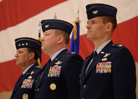 U.S. Air Force Lt. Gen. Bradley Heithold, Commander Air Force Special Operations Command, Col. Tony Bauernfeind, outgoing 27th Special Operations Wing commander, and Col. Benjamin Maitre, incoming 27th SOW commander, stand at attention before the National Anthem singing during the 27th SOW change of command ceremony, Feb. 17, 2015 at Cannon Air Force Base, N.M.  The change of command represents the closure of one chapter and the beginning of another for Air Commandos of the 27th SOW.  (U.S. Air Force photo/Airman 1st Class Chip Slack)