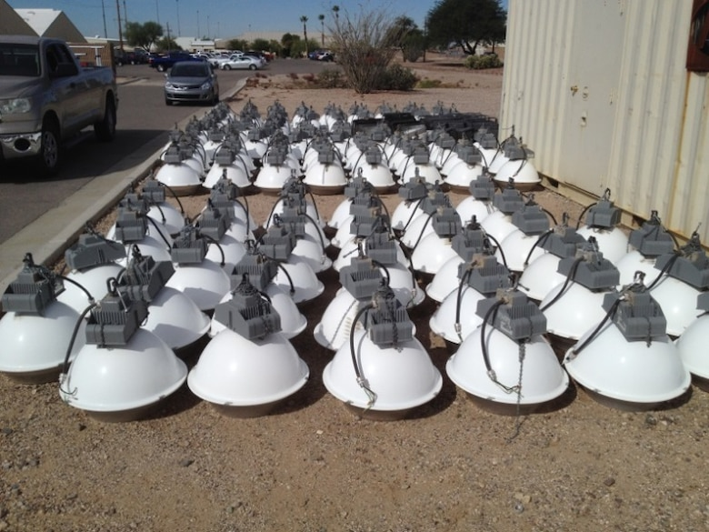 High pressure sodium lighting fixtures lie arranged on the ground at Davis-Monthan Air Force Base, Ariz. T5HO fluorescent lights replaced 675 high pressure sodium lighting fixtures as a result of energy efficiency lighting upgrades. D-M's energy efficiency programs were able to save the installation a total of $235K during fiscal year 2013, successfully exceeding the federal energy goals. (Courtesy photo)