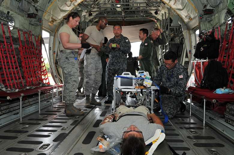 U.S. Air Force Airmen transfer a critical care patient to a Japan Air Self-Defense Force aeromedical evacuation team at Sinapalo, Rota, Feb. 16, 2015. Exercise COPE NORTH 15 enhances humanitarian assistance and disaster relief crisis response capabilities between six nations and lays the foundation for regional cooperation expansion during real-world contingencies in the Asia-Pacific Region. (U.S. Air Force photo by Staff Sgt. Melissa B. White/Released)