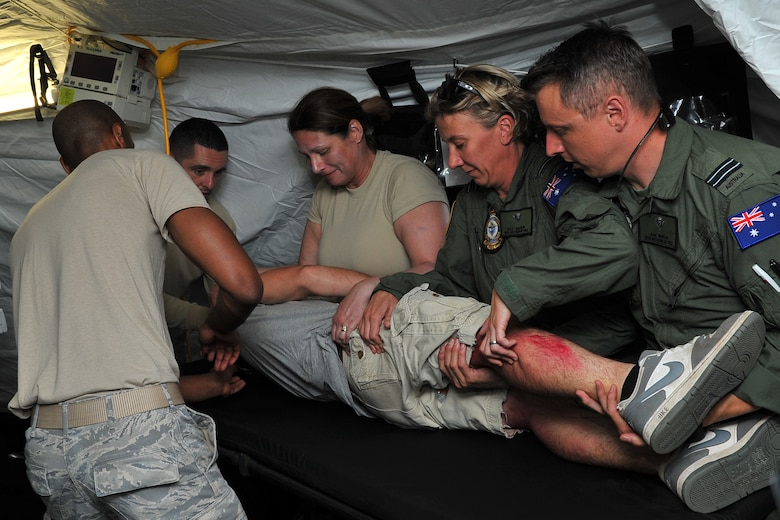 U.S. Air Force and Royal Australian Air Force medical experts assess a critical care patient for additional wounds at an expeditionary intensive care unit at Sinapalo, Rota, Feb. 16, 2015. Exercise COPE NORTH 15 enhances humanitarian assistance and disaster relief crisis response capabilities between six nations and lays the foundation for regional cooperation expansion during real-world contingencies in the Asia-Pacific Region. (U.S. Air Force photo by Staff Sgt. Melissa B. White/Released)