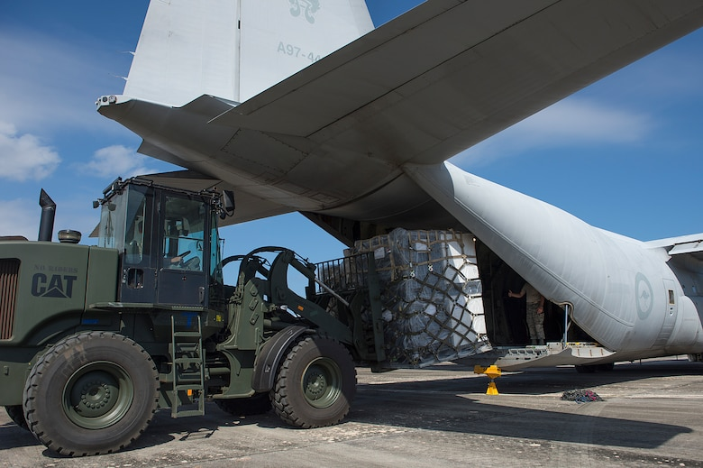 U.S. Air Force Airmen from the 36th Contingency Response Group offload cargo from a Royal Australian Air Force C-130 Hercules during a humanitarian assistance and disaster relief training event at exercise COPE NORTH 15 at Rota, Northern Mariana Islands, Feb. 15, 2015. Exercise CN 15 enhances humanitarian assistance and disaster relief crisis response capabilities between six nations and lays the foundation for regional cooperation expansion during real-world contingencies in the Asia-Pacific Region. (U.S. Air Force photo by Tech. Sgt. Jason Robertson/Released)
