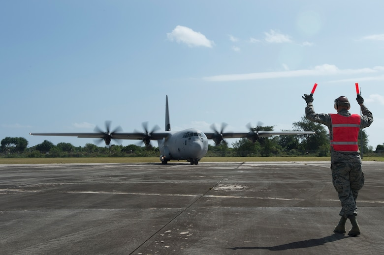 A U.S. Air Force Airman from the 36th Contingency Response Group marshals a Royal Australian Air Force C-130 Hercules into position to offload cargo during a humanitarian assistance and disaster relief training event at exercise COPE NORTH 15 at Rota, Northern Mariana Islands, Feb. 15, 2015. Exercise CN 15 enhances humanitarian assistance and disaster relief crisis response capabilities between six nations and lays the foundation for regional cooperation expansion during real-world contingencies in the Asia-Pacific Region. (U.S. Air Force photo by Tech. Sgt. Jason Robertson/Released)