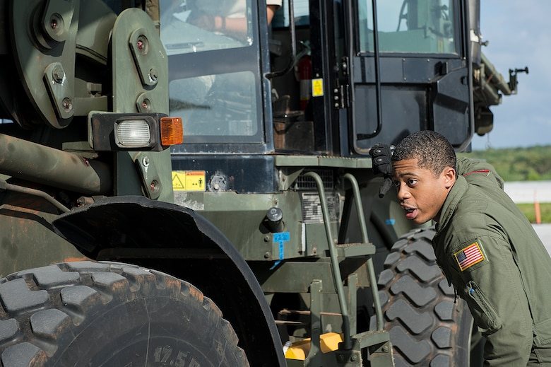 U.S. Air Force Senior Airman Gary Coe, 36th Airlift Squadron C-130 Hercules loadmaster, marshals a forklift into position to load cargo used during a humanitarian assistance and disaster relief training event at exercise COPE NORTH 15 at Anderson Air Force Base, Guam, Feb. 15, 2015. Exercise CN 15 enhances humanitarian assistance and disaster relief crisis response capabilities between six nations and lays the foundation for regional cooperation expansion during real-world contingencies in the Asia-Pacific Region. (U.S. Air Force photo by Tech. Sgt. Jason Robertson/Released)