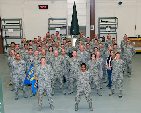 Maj. Stephanie Wilson, 90th Missile Squadron commander, stands in front of her squadron as they pose in the Weapons Storage Area, F.E. Warren Air Force Base, Wyo., Nov. 8, 2013. (U.S. Air Force file photo by R.J. Oriez)