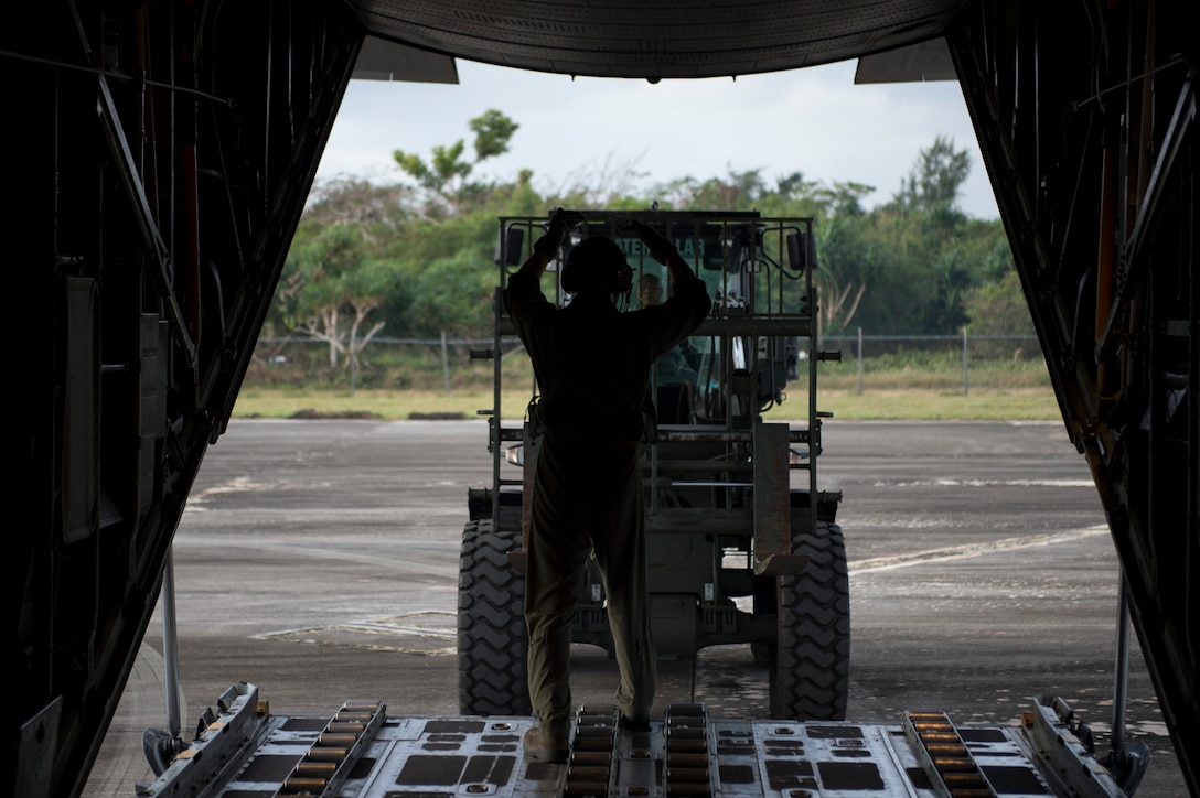Staff Sgt. Gary Patterson marshals a forklift into position to off-load cargo during a humanitarian assistance and disaster relief training event Feb. 15, 2015, at exercise Cope North 15 at Rota, Northern Mariana Islands. The exercise enhances humanitarian assistance and disaster relief crisis response capabilities between six nations and lays the foundation for regional cooperation expansion during real-world contingencies in the Asia-Pacific Region. Patterson is a 36th Airlift Squadron C-130 Hercules loadmaster. (U.S. Air Force photo/Tech. Sgt. Jason Robertson)