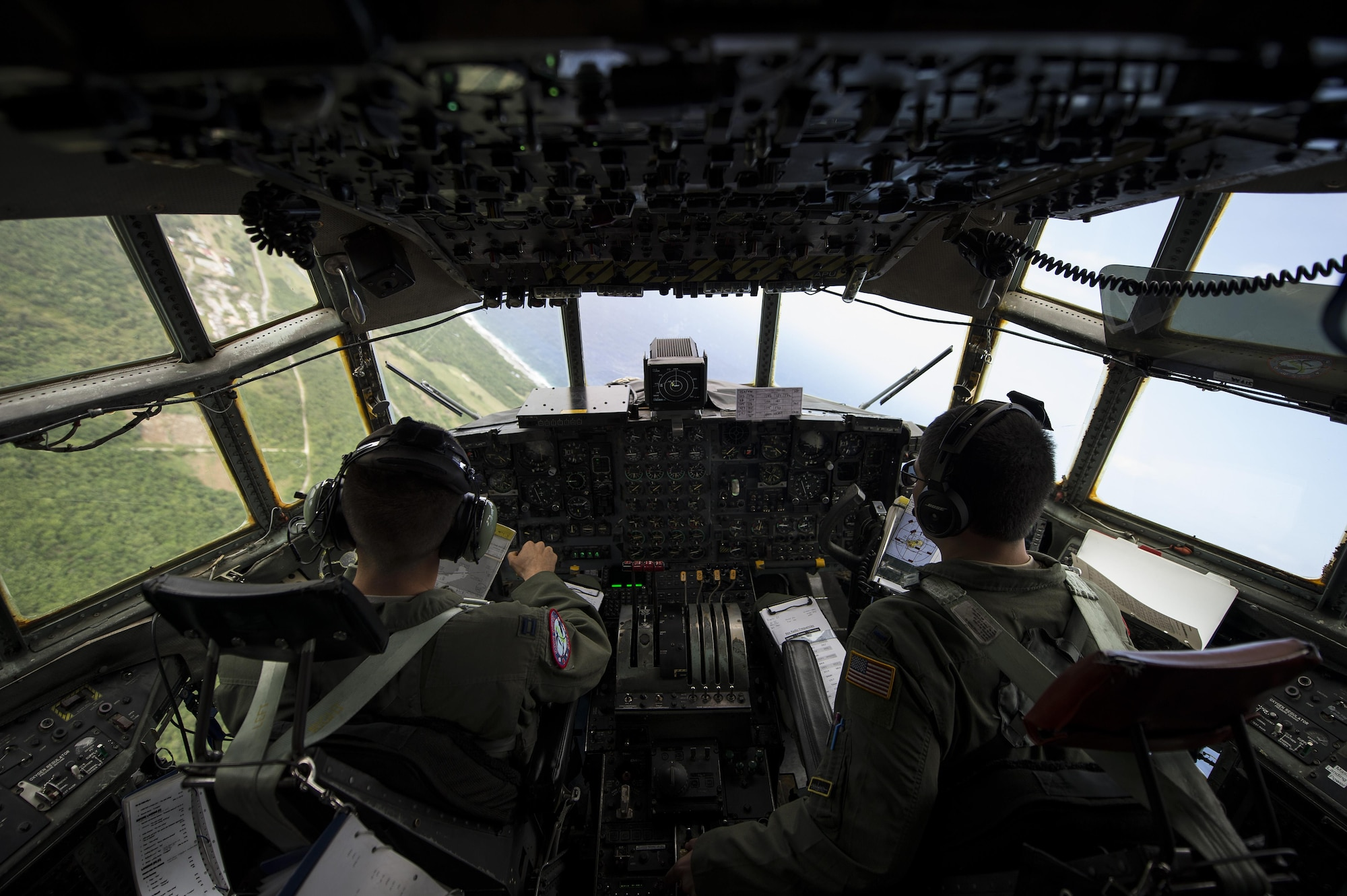 Capt. Ian Haig and 1st Lt. Eric Zane fly over Rota, Northern Mariana Islands, after delivering cargo used in a humanitarian assistance and disaster relief training event Feb. 15, 2015, during exercise Cope North 15. The exercise enhances humanitarian assistance and disaster relief crisis response capabilities between six nations and lays the foundation for regional cooperation expansion during real-world contingencies in the Asia-Pacific Region. Haig and Zane are 36th Airlift Squadron C-130 Hercules pilots. (U.S. Air Force photo/Tech. Sgt. Jason Robertson)