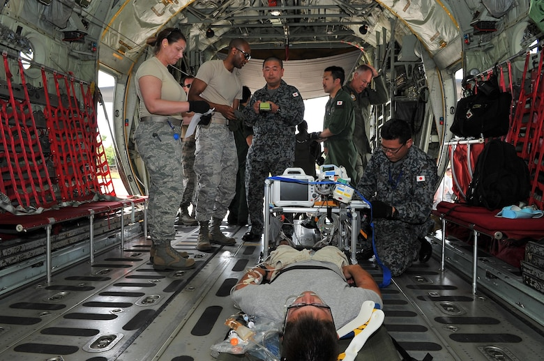 Airmen transfer a simulated critical care patient to a Japan Air Self-Defense Force aeromedical evacuation team Feb. 16, 2015, during exercise Cope North 15 at Sinapalo, Rota. The exercise enhances humanitarian assistance and disaster relief crisis response capabilities between six nations and lays the foundation for regional cooperation expansion during real-world contingencies in the Asia-Pacific Region. (U.S. Air Force photo/Tech. Sgt. Jason Robertson)