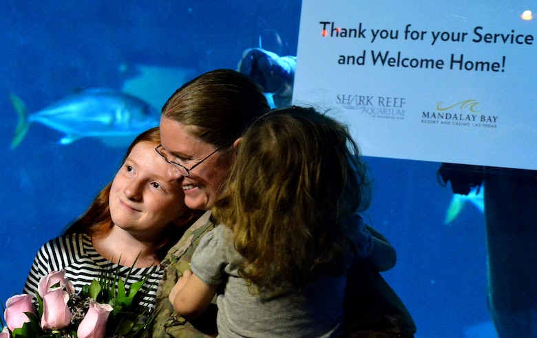 Staff Sgt. Julie Mauldin, a crew chief with the 432nd Aircraft Maintenance Squadron, hugs her daughters after surprising them with an early homecoming from a deployment to Southwest Asia, Feb. 13, 2015 at the Shark Reef Aquarium in Las Vegas. To add to the surprise, an  Aquarium scuba diver shared a sign thanking Mauldin for her service and welcoming her home. (U.S. Air Force photo by Senior Airman Adarius Petty/Released)