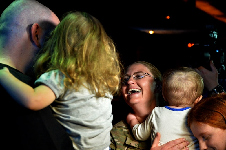 Staff Sgt. Julie Mauldin 432nd Air Craft Maintenance Squadron crew chief, center, greets her family on Feb 13. 2015, at the Shark Reef Aquarium in Las Vegas. Mauldin coordinated the surprise with local organizations after being notified that she would return home from her deployment to Southwest Asia one month earlier than planned. (U.S. Air Force photo by Senior Airman Adarius Petty/Released)