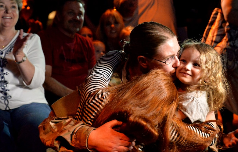 Staff Sgt. Julie Mauldin 432nd Air Craft Maintenance Squadron crew chief, kisses her daughters Caitlynn, 3, right, and Samantha, 11, after surprising on Feb. 13, 2015, at the Shark Reef Aquarium in Las Vegas. Mauldin's homecoming surprise was greeted with applause from aquarium patrons. (U.S. Air Force photo by Senior Airman Adarius Petty/Released)