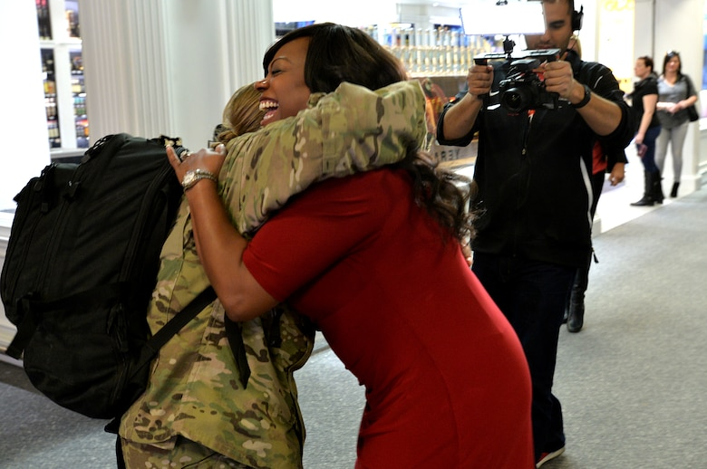 Staff Sgt. Julie Mauldin, a crew chief with the 432nd Aircraft Maintenance Squadron, is greeted by Monica Jackson, a co-anchor with Fox 5 News Surprise Squad, as she returns home from a deployment to Southwest Asia, Feb. 11, 2015, at McCarran International Airport in Las Vegas. Mauldin planned to surprise her family with her early homecoming during the family's usual visit to the Shark Reef Aquarium. (U.S. Air Force photo by Senior Airman Adarius Petty/Released)