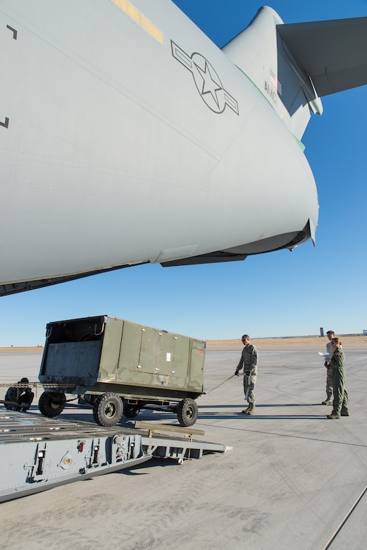 Airmen assigned to the 153rd Airlift Wing, Wyoming Air National Guard, Cheyenne, Wyoming, load cargo Feb. 11, 2015, at Buckley Air Force Base in Aurora, Colorado in support of the 140th Wing, Colorado Air National Guard deployment to South Korea.