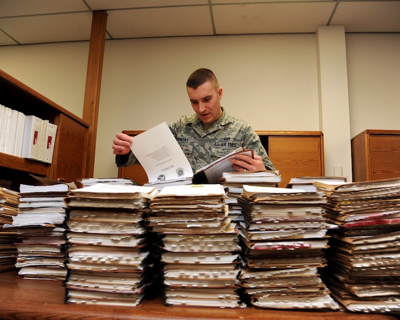 Senior Airman Alex Ponusky 319th Contracting Flight contract specialist stands amidst a mound of project files the base has completed Feb. 18, 2015 on Grand Forks Air Force Base, N.D. Ponusky responsible for all Simplified Acquisition of Base Engineering Requirements (SABER) purchases for the base (all construction projects valued under $750k). Ponusky is this week's warrior of the week for the third week of February.(U.S. Air Force photo/Senior Airman Zachiah Roberson)