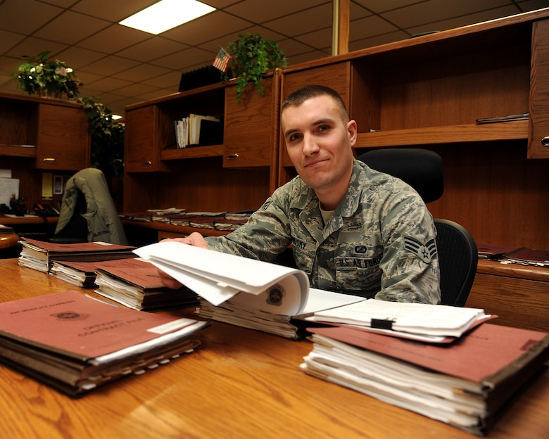 Senior Airman Alex Ponusky 319th Contracting Flight contract specialist sorts through a few of the base's open contracts dealing with projects under $750,000 Feb. 18, 2015 on Grand Forks Air Force Base, N.D. In 2014, Ponusky awarded and administered 20 projects valued at roughly $4.5Mil., with the vast majority of these projects being completed by local companies' in Grand Forks. Ponusky is this week's warrior of the week for the third week of February. (U.S. Air Force photo/Senior Airman Zachiah Roberson)