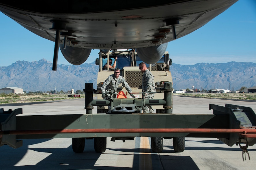 """U.S. Air Force Master Sgt. Steve Vance, 307th Aircraft Maintenance Squadron crew chief, and Tech. Sgt. Jonathan Spears, 307th Maintenance Squadron engine specialist, disconnect a tow bar from a B-52H Stratofortress on Feb. 11, 2015, Davis-Monthan Air Force Base, Ariz. The aircraft, tail number 61-007, and known as the """"Ghost Rider,"""" is being regenerated for active service after sitting in storage since 2008 when it was decommissioned and sent the Boneyard. (U.S. Air Force photo by Master Sgt. Greg Steele/Released)"""