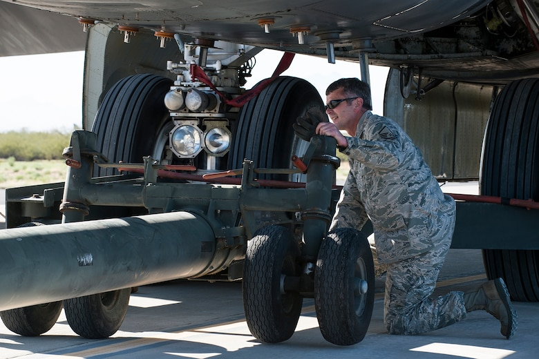 "U.S. Air Force Master Sgt. Steve Vance, 307th Aircraft Maintenance Squadron crew chief, disconnects a tow bar from a B-52H Stratofortress after towing it to a parking spot on the flight line at Davis-Monthan (DM) Air Force Base, Ariz., Feb. 11, 2015. The aircraft was decommissioned in 2008 and sent to the ""Boneyard"" at the 309th Aerospace Maintenance and Regeneration Group at DM, but is now being restored and is expected to return to active service in 2016. (U.S. Air Force photo by Master Sgt. Greg Steele/Released)"