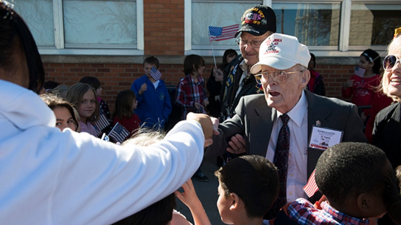 "Cecile ""Cy"" Young, a U.S. Navy veteran and survivor from the battle of Iwo Jima, is greeted by students and staff from Sheppard Air Force Base Elementary School at Sheppard Air Force Base, Texas, February 13, 2015. Survivors were treated to a special program performed by students at the school."