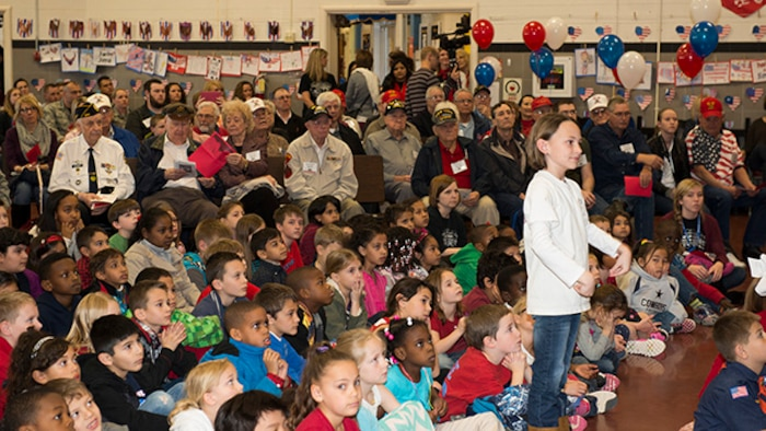 Survivors from the battle of Iwo Jima and students at Sheppard Air Force Base Elementary School listen to a special program perfomed for survivors of the battle of Iwo Jima during the 70th Iwo Jima Veteran's Program by the Sheppard Choir at Sheppard Air Force Base, Texas, February 13, 2015. Students sang special songs for the event and sixth grade students read poems they wrote for the occasion.