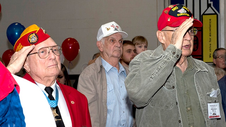 "Hershel ""Woody"" Williams, Marine survivor from the battle of Iwo Jima and the last living Medal of Honor recipient for his actions during the battle, and William ""Bil"" Schott a Marine survivor from the battle of Iwo Jima, salute during the singing of the Star Spangled Banner during the 70th Anniversary Iwo Jima Veteran's Program at Sheppard Air Force Base Elementary School, Sheppard Air Force Base, Texas, February 13, 2015. The students at the school performed a program with the Sheppard Choir singing songs and the sixth graders reading poems they wrote."